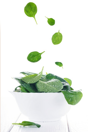 Flying food spinach leaves in bowl on white, floating food summer concept Stock Photo