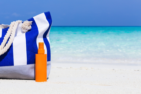 Summer hat and blue stripe bag with sunscreen lotion on sandy tropical beach with turquoise sea background