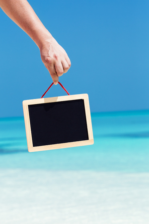 Empty board with copy space hanging in hand on beach tropical vacation background, travel banner, space for text, mock up, blank blackboard for your advertising content Stock Photo