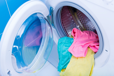 Washing machine at bathroom, stainless drum inside with colored clothes.