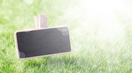 Blank mockup board on green grass background, closeup
