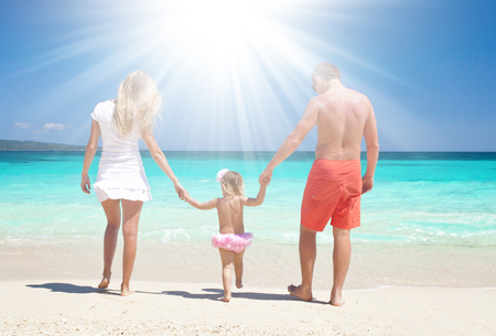Mother, father and daughter having fun on tropical white beach