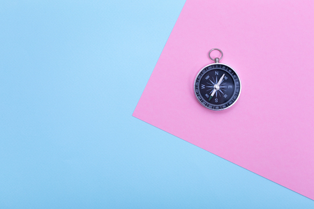Compass on pastel colored paper texture, flat lay  Stock Photo