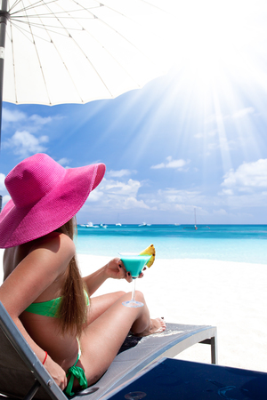 Woman in sunhat sitting in chaise longue with glass of cocktail. Travel destinations