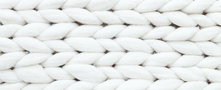White texture textile background from merino knitted blanket, scandinavian minimalism backdrop with copy space, top view