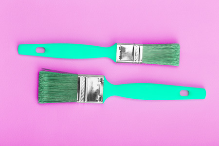 Two green brushes for painting on pink colored paper texture, flat lay
