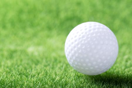 White golf ball on green grass background, closeup  Stock Photo