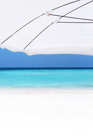 Detail of parasol on white sandy sunny beach with sea view, travel tropical copy space background for your text, nobody, mock up