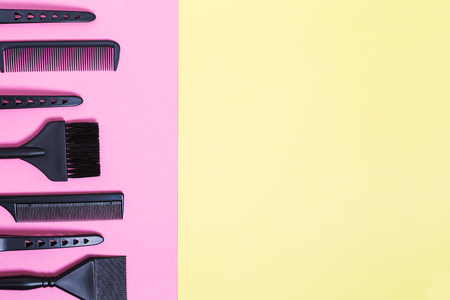 Hairdresser tools with copy space, combs and bleach brushes on pastel colored paper background, top view and flat lay