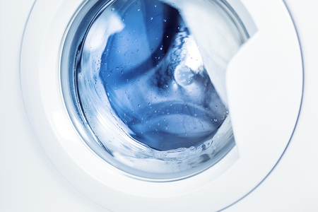 Detail of washing machine at bathroom, cleaning clothing process, stainless drum inside, closeup, nobody