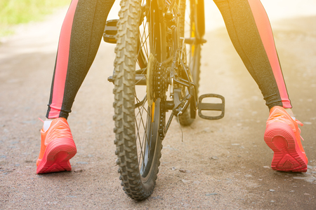 Woman riding a mountain bicycle along path at park. Closeup on pedal and foot. Healthy lifestyle and sport concept