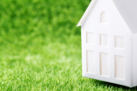 Hunting house concept. Model of white paper house on green grass background  Stock Photo