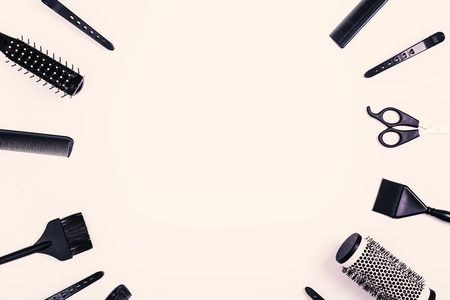 Hairdressing tools with copy space, combs and bleach brushes on white background, top view and flat lay, toned image