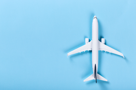White blank model of passenger airplane on serenity colored paper texture, flat lay