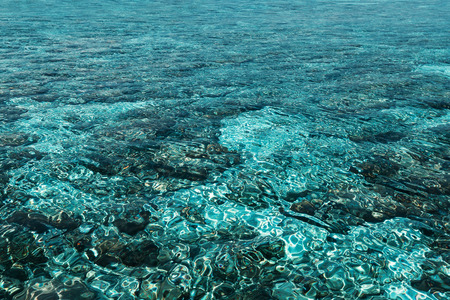 Crystal pure azure water in ocean with coral reefs, sea texture and nature background concept