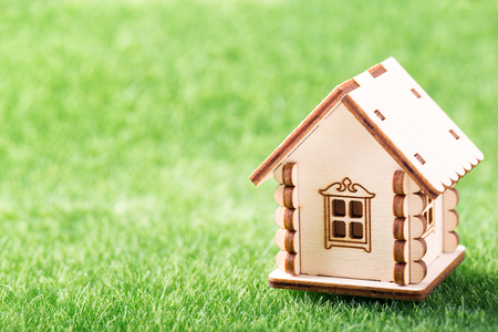 Mortgage concept. Model of wooden house on green grass background