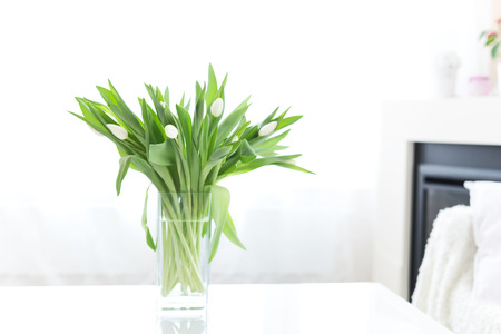 Bouquet of tulips in glass vase on table at home