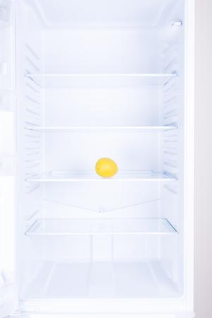 Lemon fruit on glass shelf inside in empty clean refrigerator with opened door, nobody