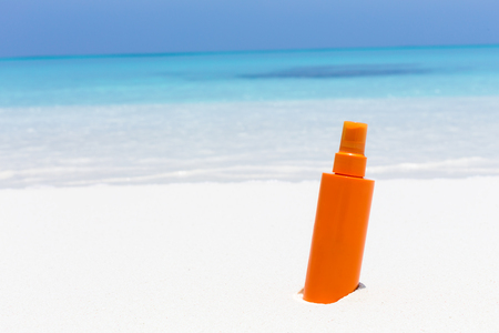 Skin care on summer vacations. Tube with sun screen SPF protection lotion on tropical sea shore. Copy space for your text Stock Photo