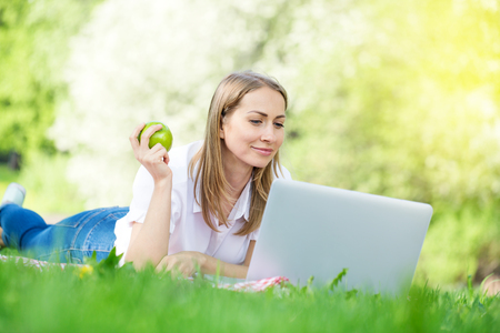 Young blond woman lying on a grass in the park using laptop and working, holding green apple, female freelance concept Stock Photo