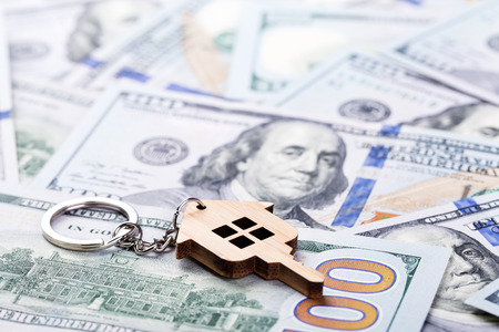 Mortgage concept. Wooden key chain on dollar banknotes background