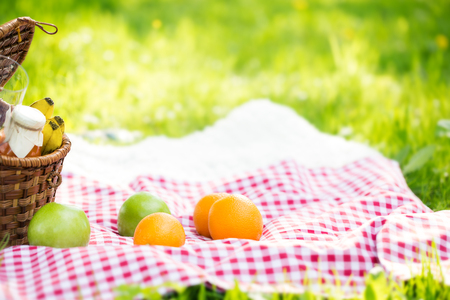 Wicker basket on red checkered tablecloth with fruits on grass, vegan picnic with healthy food in park outside at summer day