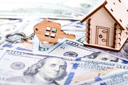 Mortgage concept. Wooden model of house and key chain on dollar banknotes background