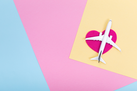 White blank model of passenger airplane on shapes of heart over serenity colored paper texture, flat lay
