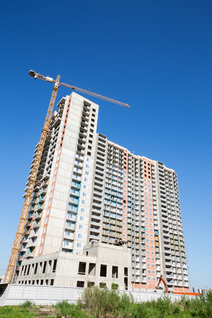 Building under construction. Crane move heavy tools. Outdoors