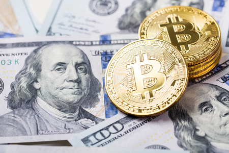 Bitcoins on dollar banknotes background, closeup