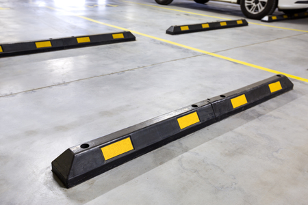 Underground car parking at modern house. Closeup on rubber hurdle. Nobody