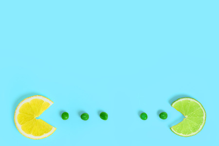 Lemon and lime fruits eating green peas on creative color paper background. Trendy minimal pop art style. Concept of funny colorful food. Stock Photo