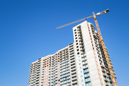Building under construction. Crane move heavy tools on blue sky background