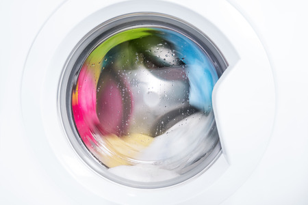 Process of cleaning color cloth in washing machine, stainless drum inside with wet towels, closeup, nobody