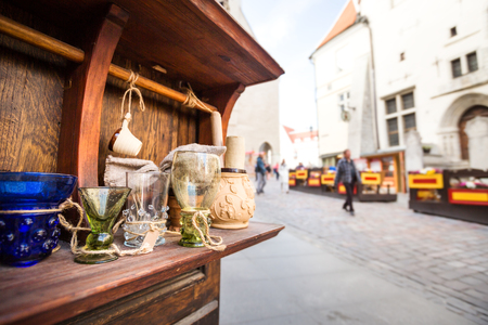 Old medieval glass cups souvenirs on wooden shell at historic Hall Square at sunny day, Tallinn city
