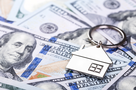Mortgage concept. Metal Key chain on dollar banknotes background