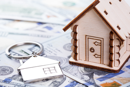 Mortgage concept. Wooden model of house and metal key chain on dollar banknotes background Stock Photo