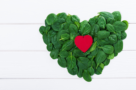 Heartshaped sign made of fresh greenery spinach leaves with red heart inside green symbol, top view Stock Photo