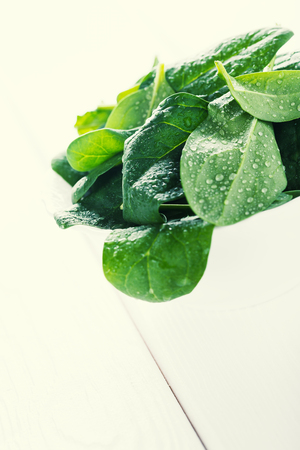 Fresh raw organic baby spinach in bowl on wooden board, diet concept, toned image