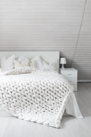 Cozy white scandinavian bedroom interior at mansard cabin. Beautiful merino woolen plaid decorated bed and floor, super chunky yarn knitted blanket, nobody