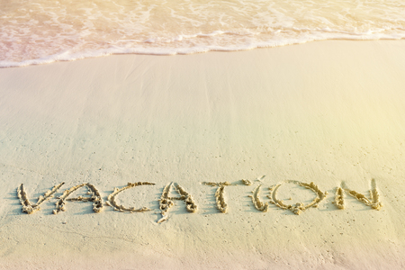 Handwritting inscription Vacation word on tropical sandy beach, travel concept card for  holidays Stock Photo