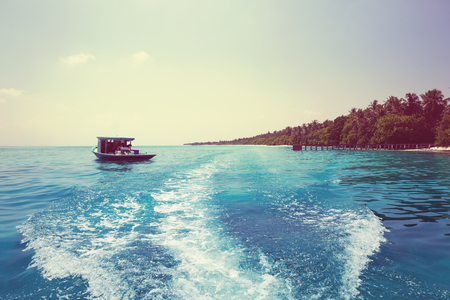 Rear view of waves behind the speedy boat of fast moving in azure sea at tropical nature. Ocean water ship trail with white foamy wave, ferry travel to maldivian islands.