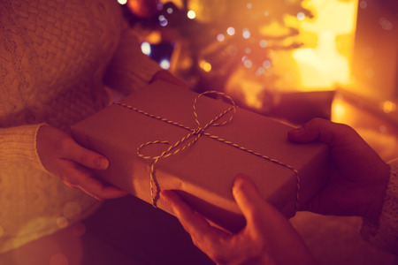 Christmas gift in hands, winter holidays celebration, New Year present on fireplace background, no face