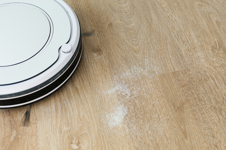 Robot vacuum cleaner cleaning laminate floor in room, nobody