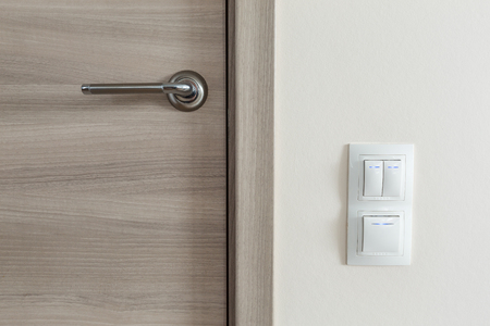 Door handle and white lighting switches on wall at modern apartment Stock Photo