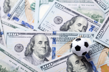 Soccer ball on dollar banknotes, closeup. Betting on sport concept