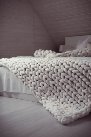 Cozy white scandinavian bedroom interior. Beautiful merino woolen plaid decorated bed and floor, super chunky yarn knitted blanket, nobody, toned image