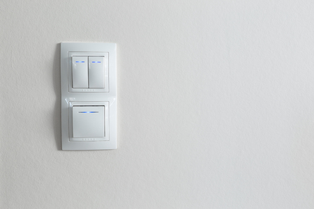 Three white lighting switch on wall at modern apartment Stock Photo