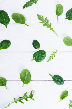 Greenery trendy color composition, top view of baby spinach and arugula leaves on white wooden background, flat lay