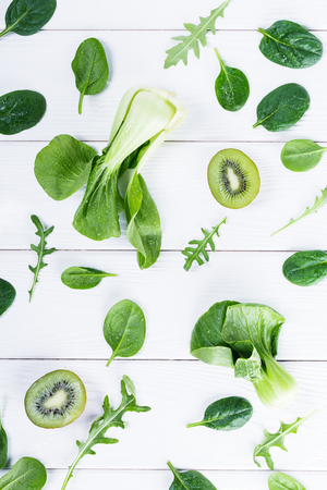 Top view composition of green pok choy, kiwi fruit and fresh lettuce, arugula and spinach, flat lay